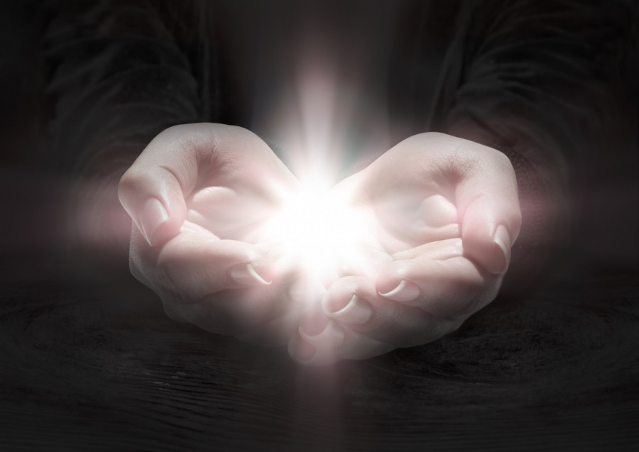 Hands opening and holding a light inside them.